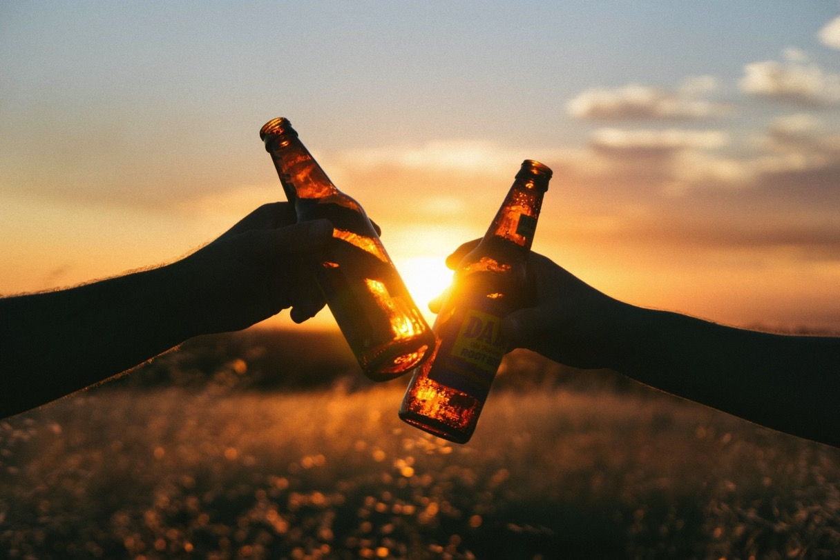 2 friends toasting with beer bottles in meadow at sunset